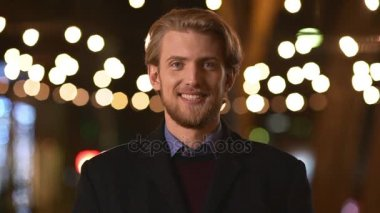 Young confident handsome Caucasian male with light beard and dark coat smiling at camera than pointing two fingers in slowmotion