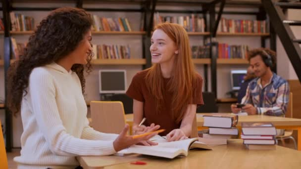 teenage girls sitting at table in library