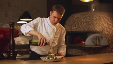 šéf kuchař odlévání olivový olej z láhve