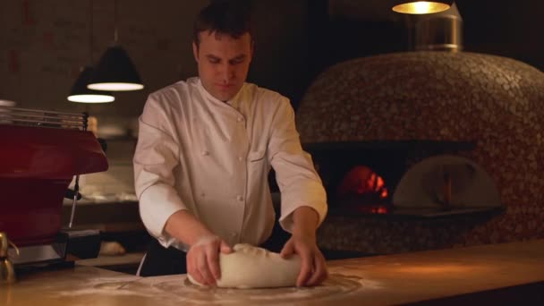 baker beating dough on wooden table