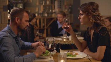lovers sitting at restaurant drinking wine