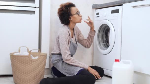 Frau versucht zu sortieren, wie Sie die Waschmaschine benutzen