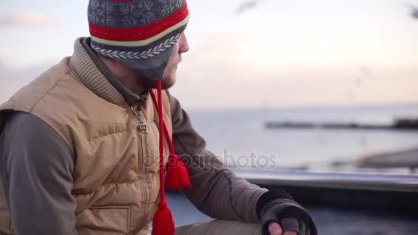 muž sedí blízko moře