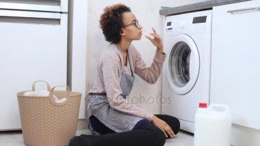 Žena se snaží vyřešit jak používat pračku