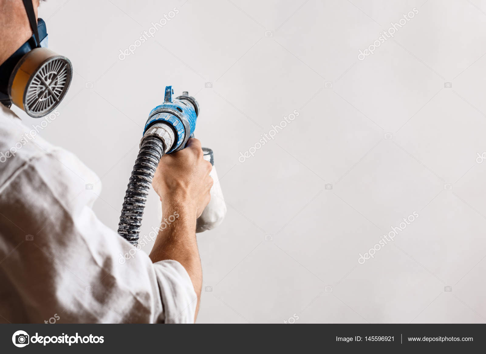 Mur De Peinture Du Travailleur Avec Pistolet Dans La Couleur