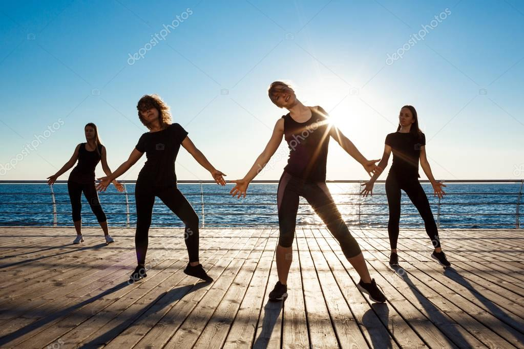 Silhouettes of sportive girls dancing near sea at sunrise.