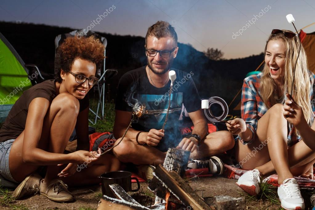 Friends sitting near bonfire, smiling, playing guitar. Camping grill marshmallow.