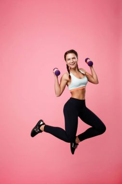 Young excited woman jumping up with purple dumbbells looking straight