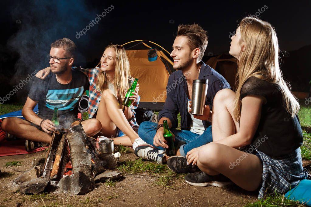 Friends sitting near bonfire, smiling, speaking, resting, drinking bear. Camping.