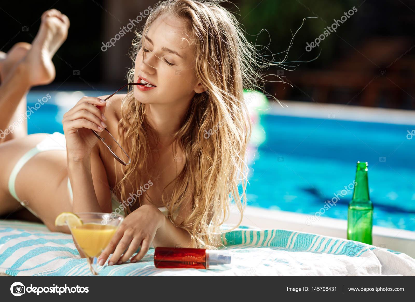 3949a9853 Hermosa chica rubia en traje de baño tomando el sol