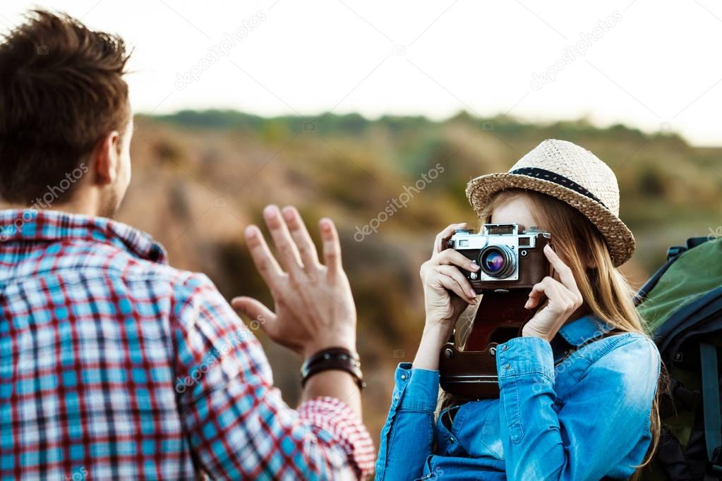 Beautiful blonde female photographer taking picture of boyfriend, canyon background.
