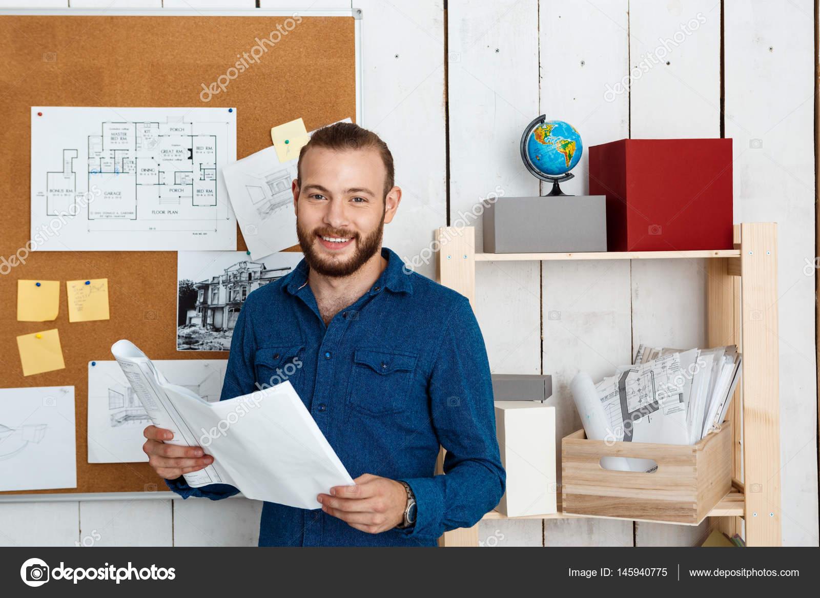 Capo Ufficio Disegno : Giovane studente successo sorridente che tiene di disegni in piedi