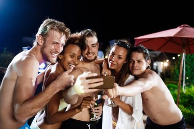 Young cheerful friends smiling, rejoicing, making selfie, resting at party.