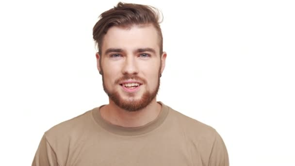 Hezký bělochovi v khaki tričko a hnědé vousy usmívat a říkat ano na bílém pozadí