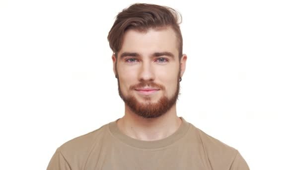 Hezký zmrzlého muže s vousy hnědé a khaki tričko, usmívající se na bílém pozadí