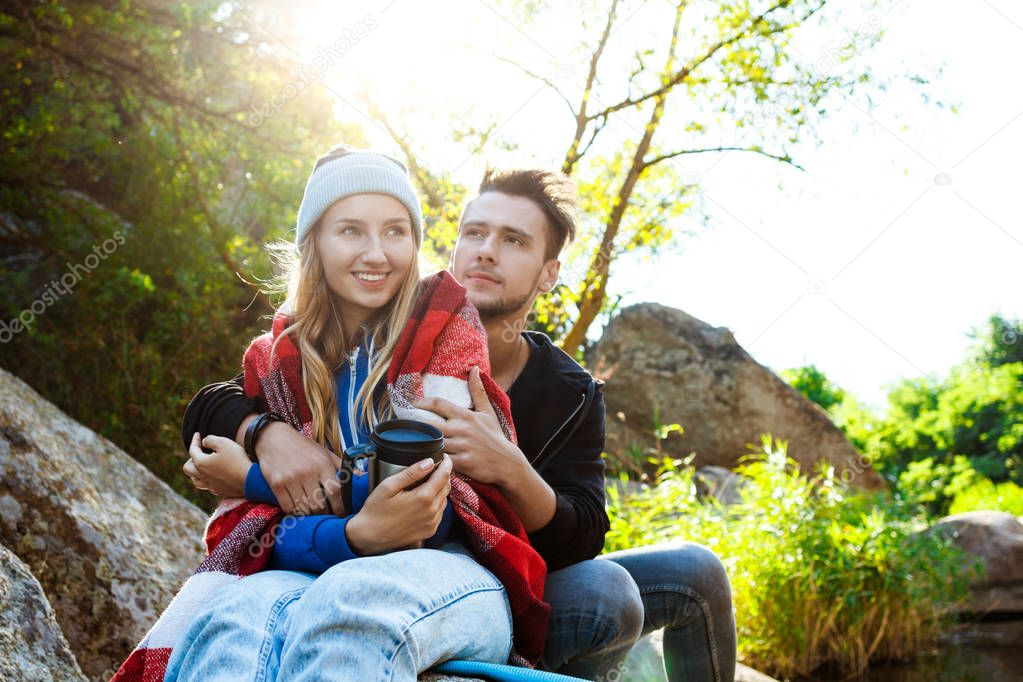 Young couple sitting on rock in canyon, smiling, drinking tea.