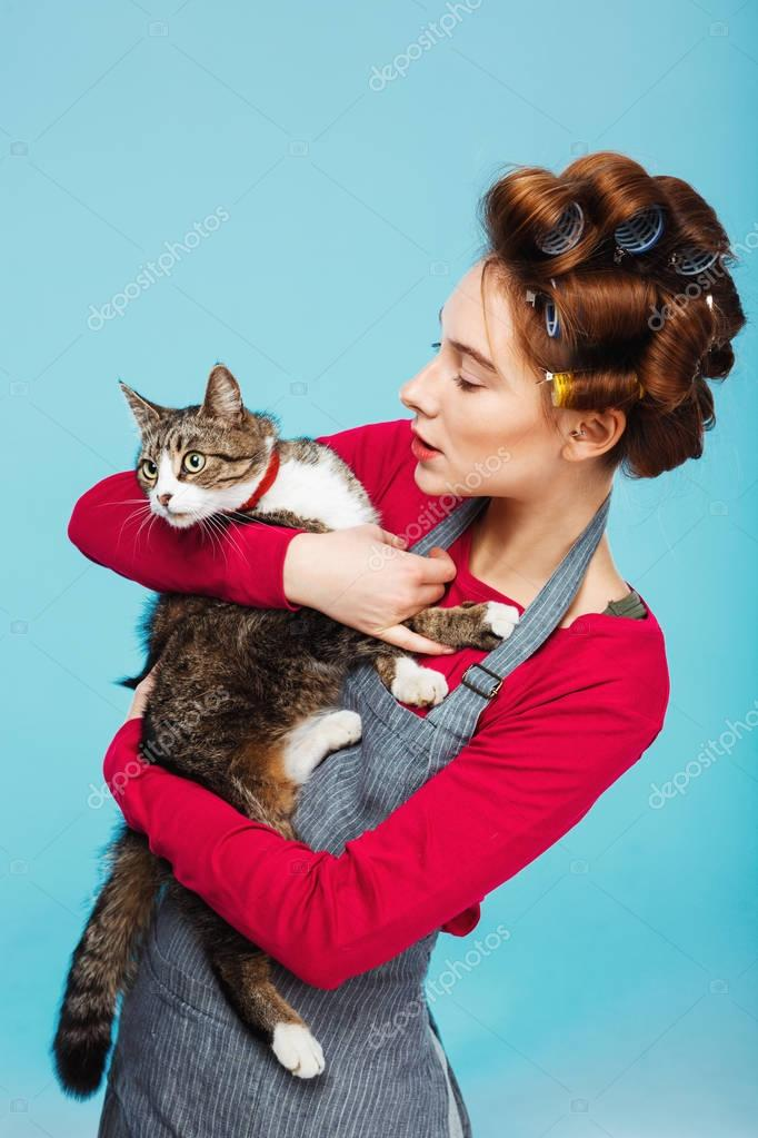 Woman and cat pose for picture together while cleaning