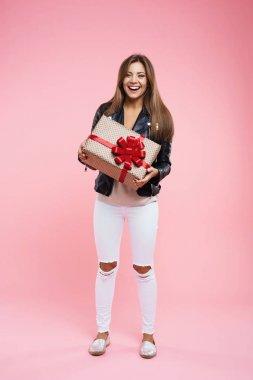 Happy teenage girl in basic look holding birthday gift