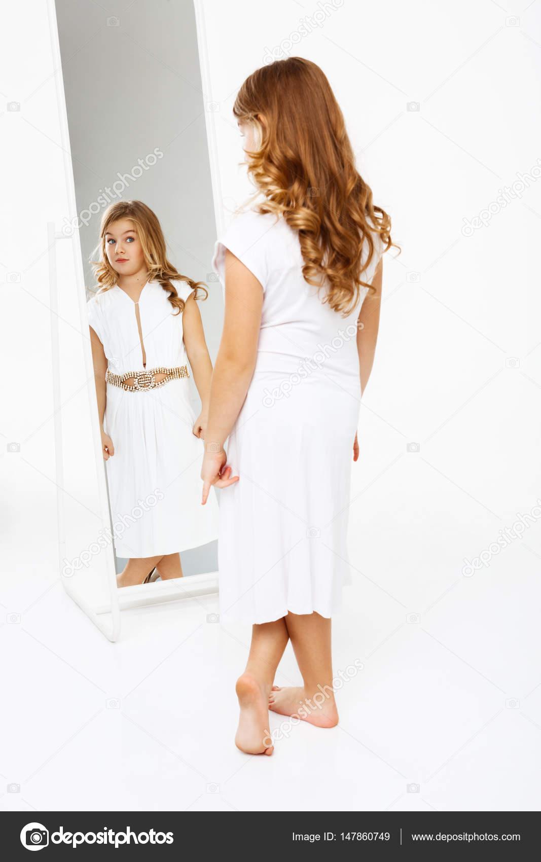 Bella ragazza in vestito in piedi davanti allo specchio - Ragazza davanti allo specchio ...