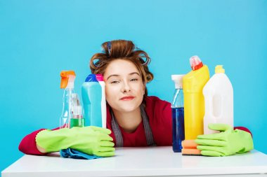 Young cheerful housewife and daily routine on blue background