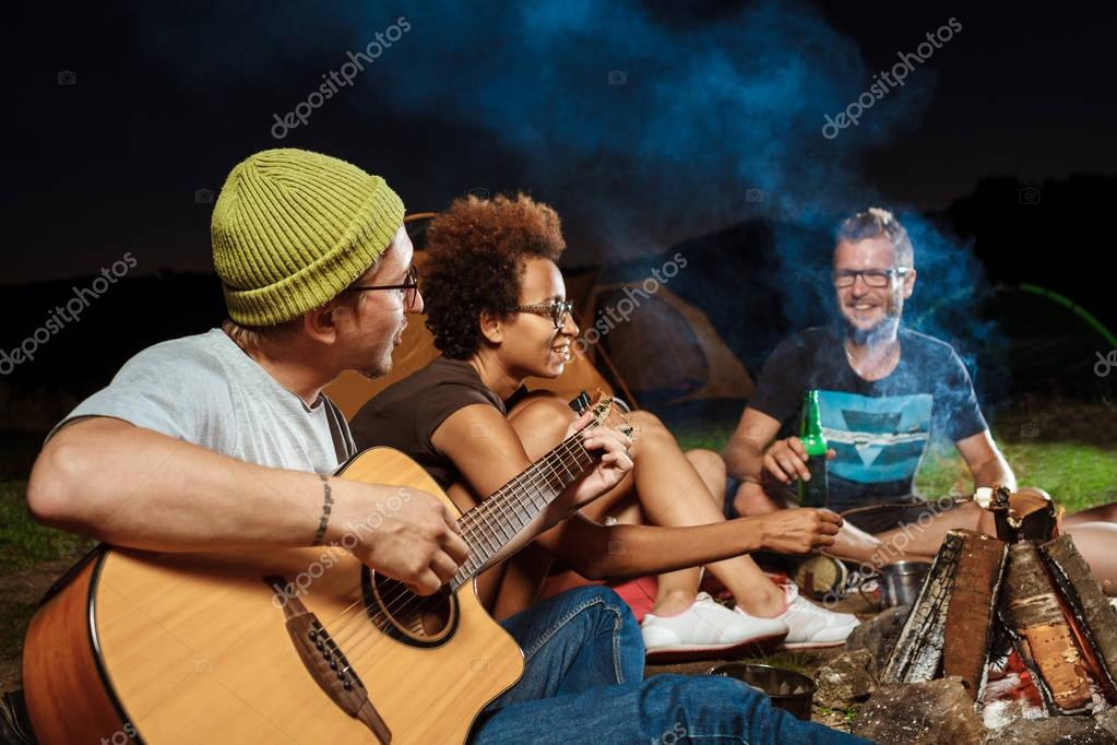 Friends sitting near bonfire, smiling, speaking, resting, playing guitar. Camping.