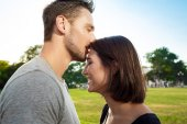 Young beautiful couple smiling, relaxing, kissing in park.