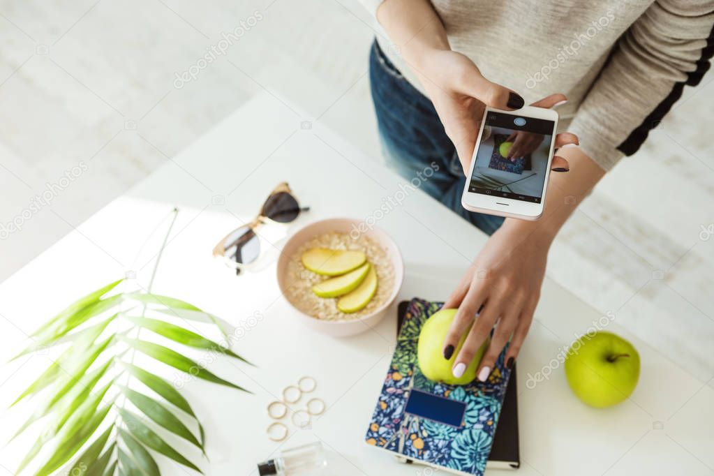 Stylish girl taking pictures with apple, notebook on whie table.