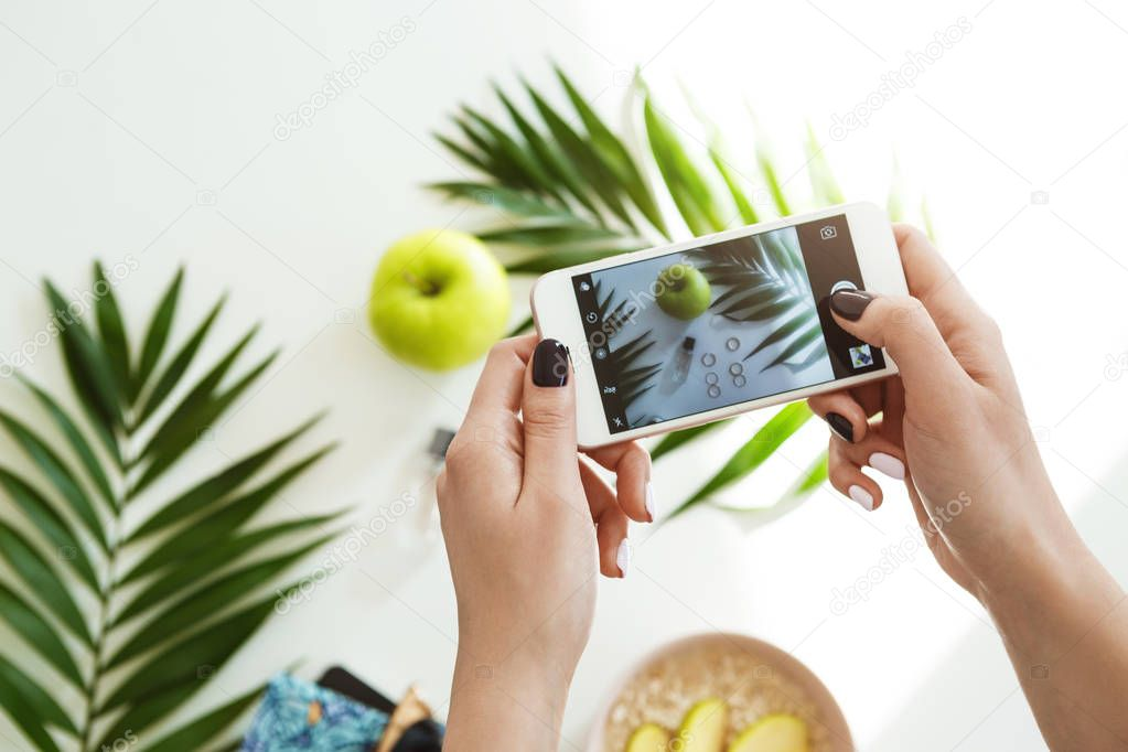 Woman hands with stylish nail polish holding phone taking pictures.