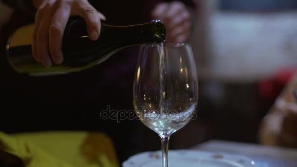 Detailní záběr záběry vína z láhve do skla v slowmotion