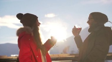 Caucasian male and female standing with glasses of wine talking laughing in slowmotion. Footage with mountains on background and sun flare