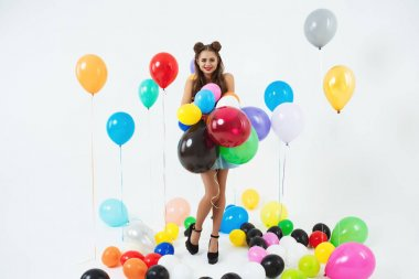 Stylish female hipster posing with big balloons on white