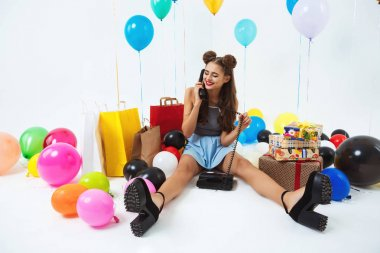 Girl sitting on floor with home phone, receiving birthday wishes