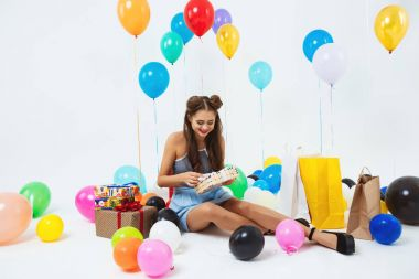 Glad girl uncovering birthday present boxes sitting with helium balloons