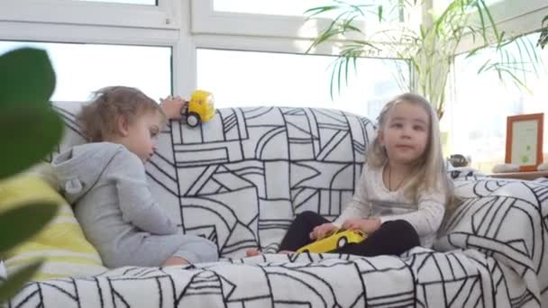 Two cute boy and girl Caucasian babies sitting on sofa and playing with toy cars