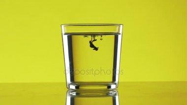 A fekete festék csöpögött a két kis csepp tiszta víz az üveg állandó sárga alapon slowmotion