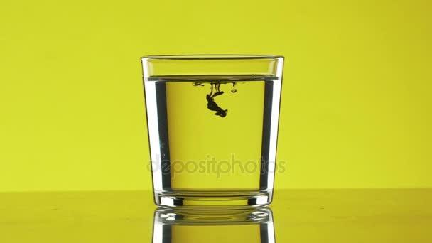 Zwei kleine Tropfen schwarze Tinte tropft in klarem Wasser im Glas stehen auf gelbem Hintergrund in slowmotion