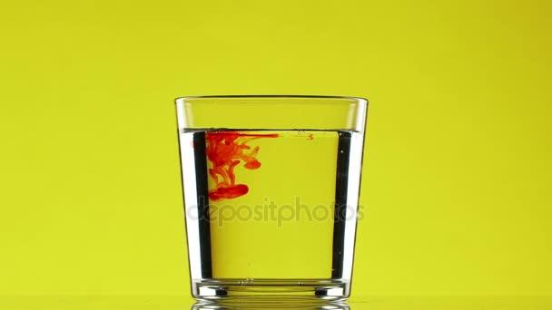 Kapku červeného inkoustu kape do sklenice s čistou vodou na žlutém podkladu v slowmotion