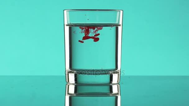Goccia di inchiostro rosso gocce nellacqua libera in vetro in piedi sul fondo del turchese in slowmotion