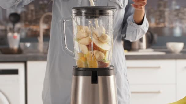 female adding milk to blender with pieces of fruits