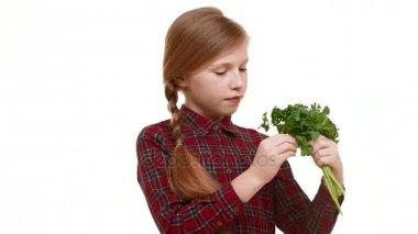 dívka s copánkem na vlasy drží spoustu zeleně