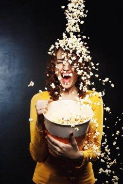 Popcorn shower. Girl having fun with friends, throwing popcorn