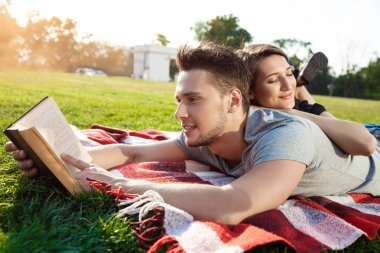 couple smiling, reading, resting on picnic