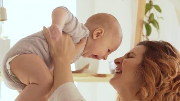 female holding infant baby boy kissing