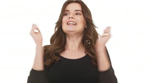Radostné Kavkazský žena s dlouhé tmavě hnědé vlasy, šťastně říct wow na bílém pozadí a usmívá se slowmotion