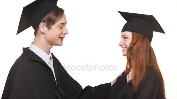 Happy kavkazských postgraduální chlapec a dívka v černém rouchu a čtvercové akademické čepice vzájemně povzbuzovali usmívající se smát na bílém pozadí
