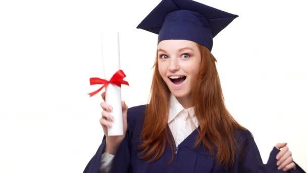 Vzrušující kavkazských zázvor postgraduální dívka v modrém šatu a čtvercové akademický víčko zobrazení posouvání diplom a radost v bílém pozadí