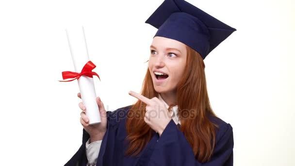 Vzrušující kavkazských zázvor postgraduální dívka v modrém šatu a čtvercové akademický čepici ukazující diplom svitek a radost v bílém pozadí v slowmotion