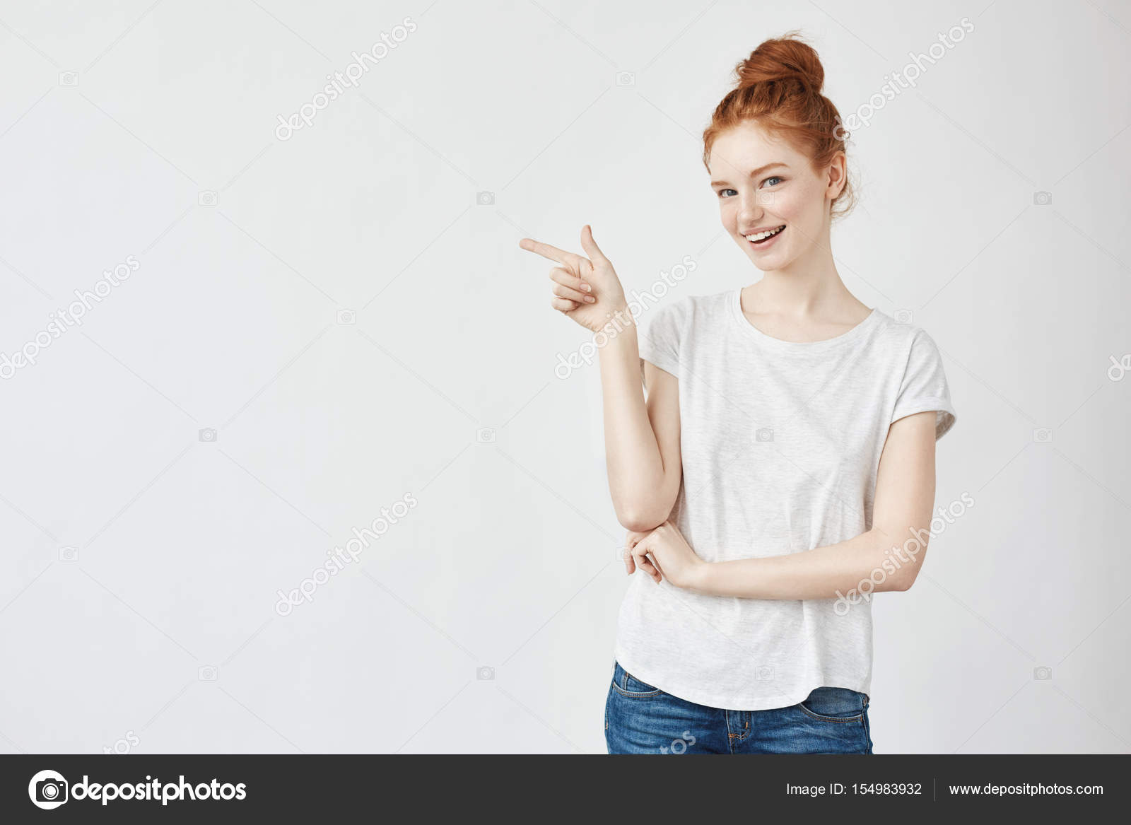 50e305f1d1 Young beautiful girl with foxy hair and freckles smiling pointing finger in  side looking at camera. Copy space. Isolated on white background.