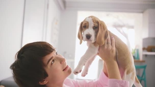 Detailní záběr záběry z kavkazské mladé ženské hrát s beagle štěně ve světle ložnici v slowmotion