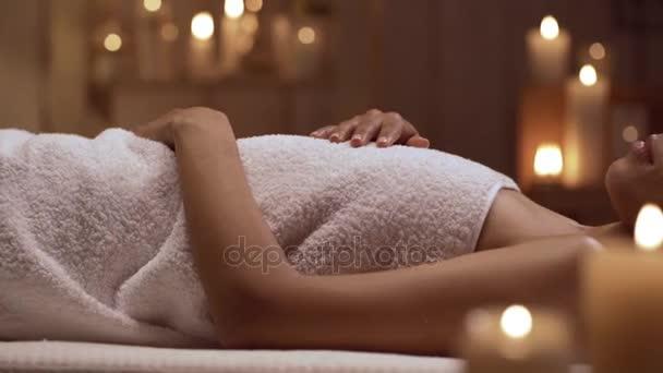 Relaxační, afroamerické ženy leží v denní lázně a ejoying masáž hlavy